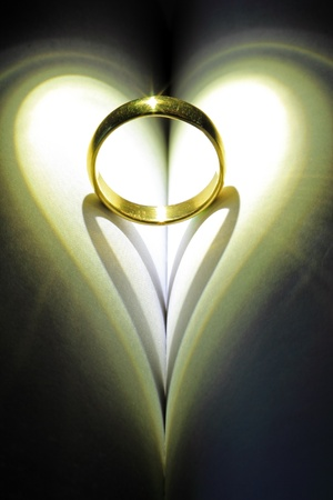 christian marriage: Golden ring casting a heart shaped shadow