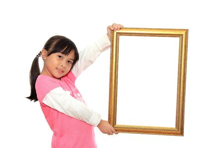 Happy little girl holding a blank picture frame on white background photo
