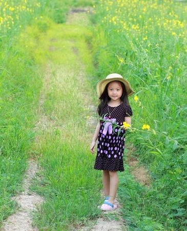 Portrait of beautiful happy little girl in a field of yellow flowers Stock Photo - 13485100