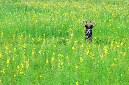 Portrait of beautiful happy little girl in a field of yellow flowers photo