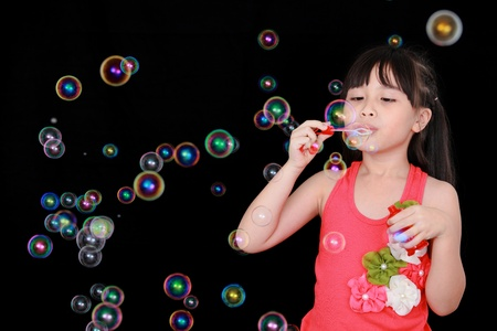 girl blowing: Happy girl play with soap bubbles isolated black background Stock Photo