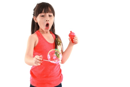 Happy girl play with soap bubbles isolated white background photo