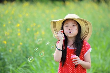 Gelukkig meisje spelen met zeepbellen op gele bloem veld. Stockfoto