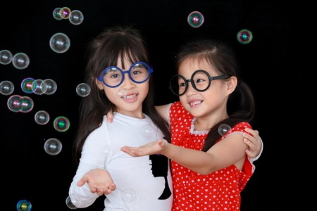 Two happy girl play with soap bubbles isolated black background photo