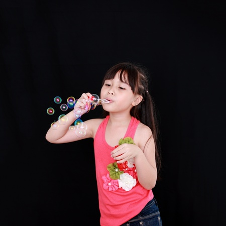 Happy girl play with soap bubbles isolated black background photo