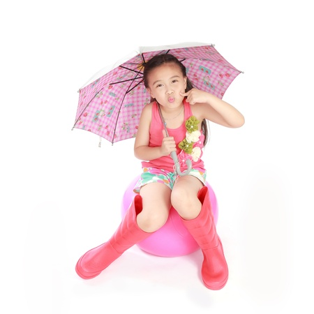 smiling little girl with umbrella and boots on white background