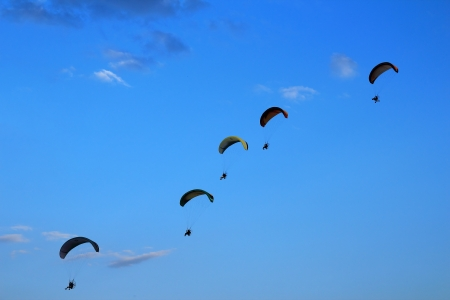 high powered: Paragliding against clear blue sky