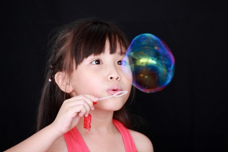 blowing bubbles: Happy girl play with soap bubbles isolated black background Stock Photo