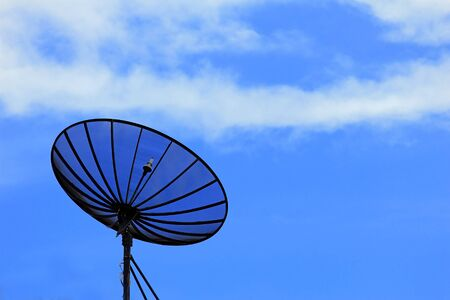 Satellite dish under blue sky photo