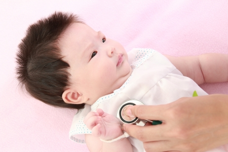 asian hospital: Doctor exams baby with stethoscope Stock Photo