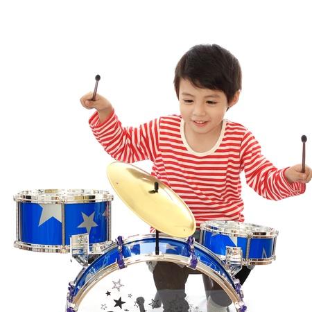 tambor: Chico joven asiático que juega el tambor azul sobre fondo blanco Foto de archivo