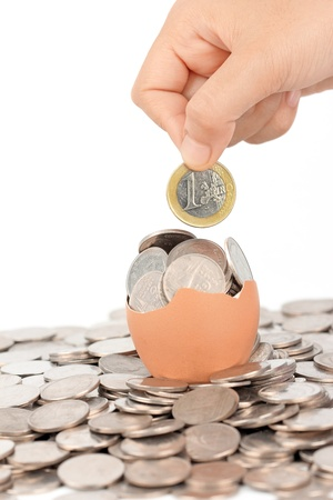 hand keep euro coin on broken eggshell photo