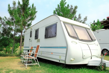 Caravan: Travel Trailer with chair in the nature Stock Photo