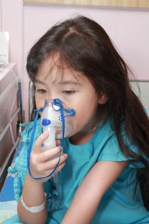 Little girl with a mask for inhaler in hospital Standard-Bild