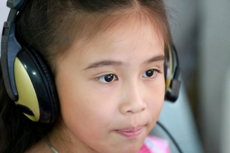 Little girl using laptop with headphone photo