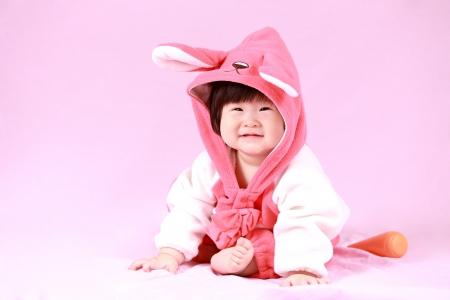 baby gekleed in Easter bunny oren met wortel