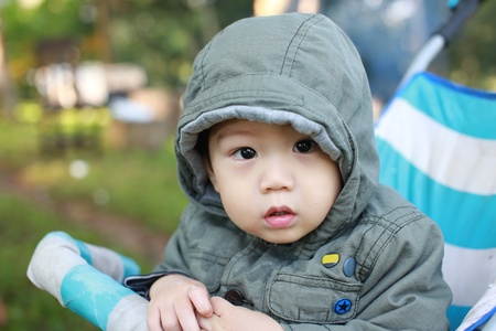 little asian boy with winter coat in baby stroller  photo