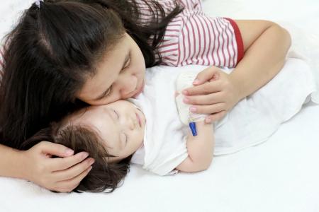 Ziek kind in de armen van haar moeder.