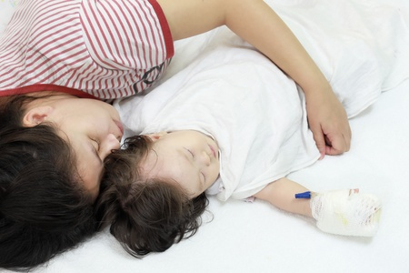 child in bed: Sick child in her mothers arms.