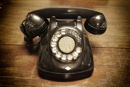 antique phone: old telephone with rotary dial on old wooden Stock Photo