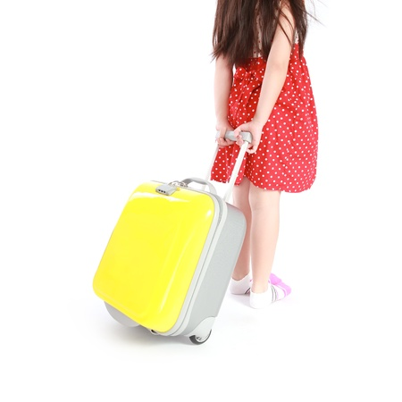 Portrait of little girl with travel case isolated on white background Foto de archivo