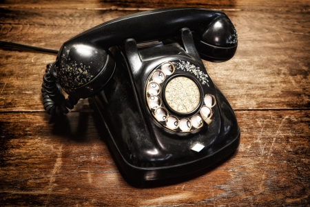 old telephone with rotary dial on old wooden photo