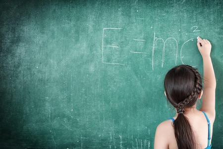 girl drawing E=mc2 on chalkboard photo