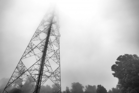 telecom: communication antenna tower in the mist Stock Photo