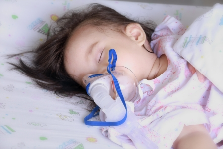 baby girl with a mask for inhaler in hospital.