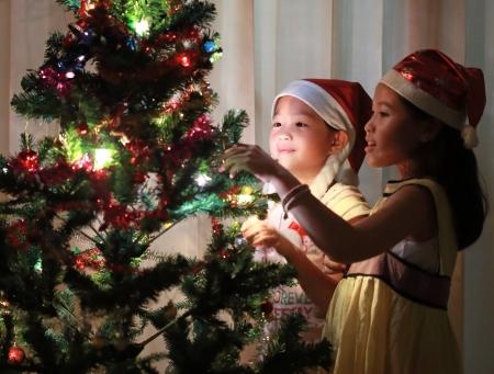 Portrait of happy girl decorating Christmas tree