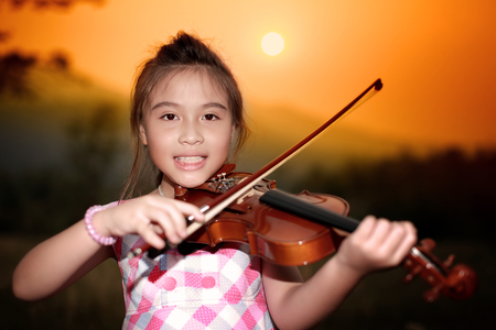 beautiful girl playing violin in nature photo