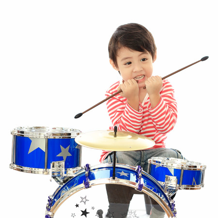 Asian young boy playing drum on white background photo
