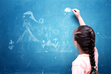 girl drawing my family on chalkboard