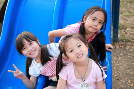 Three happy smiling children playing in park