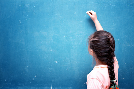 female kid: girl drawing on blank chalkboard