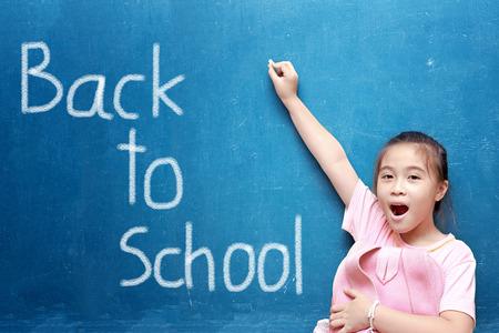 kids writing: girl drawing back to school on chalkboard
