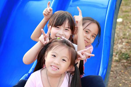 Drie gelukkige lachende kinderen spelen in het park Stockfoto