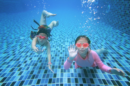 girl underwater: weinig Aziatisch meisje onderwater in zwembad Stockfoto