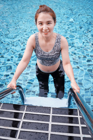 Young pregnant woman in swimming pool photo