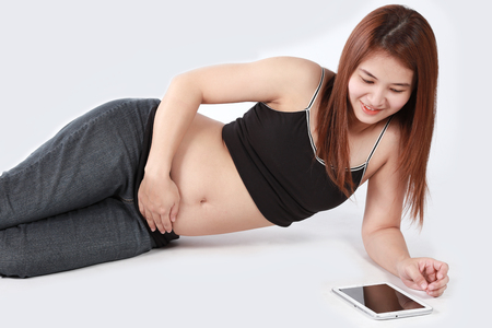 Beautiful Asian pregnant woman using tablet computer isolated white background photo