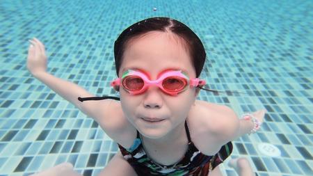 girl underwater: Weinig Aziatisch meisje onderwater in zwembad