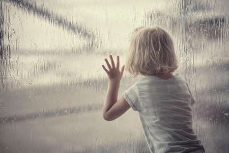 Child girl looking at raindrops on the window photo