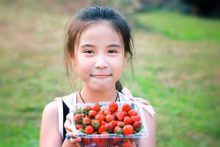 niños chinos: Niña comiendo fresas Foto de archivo