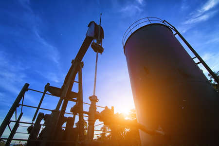 Oil pump or oil energy industrial machine for petroleum in the sunset photo