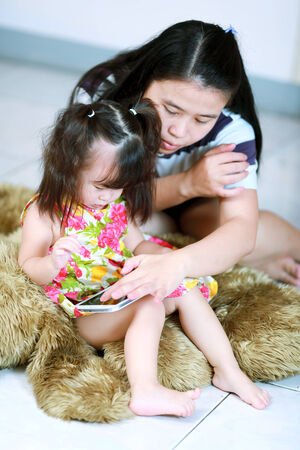 Mother and baby girl using tablet computer photo