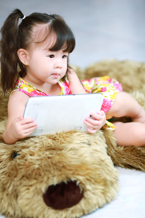 Happy baby girl using tablet computer photo
