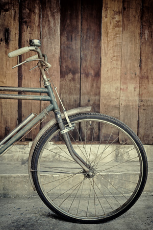 vintage bicycle leaning against wooden wall photo