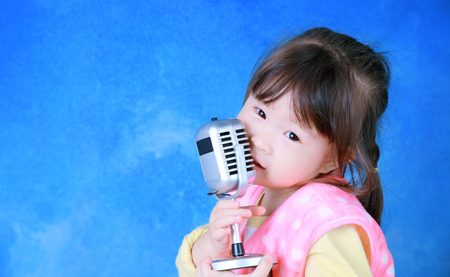 Happy little girl with retro microphone photo