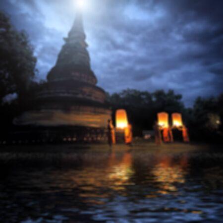 sky lantern: monk floating sky lantern with water reflection blur background
