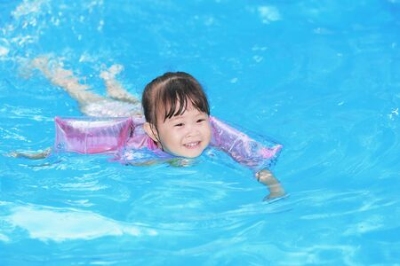 cute little girl smiling: Happy little girl in the pool